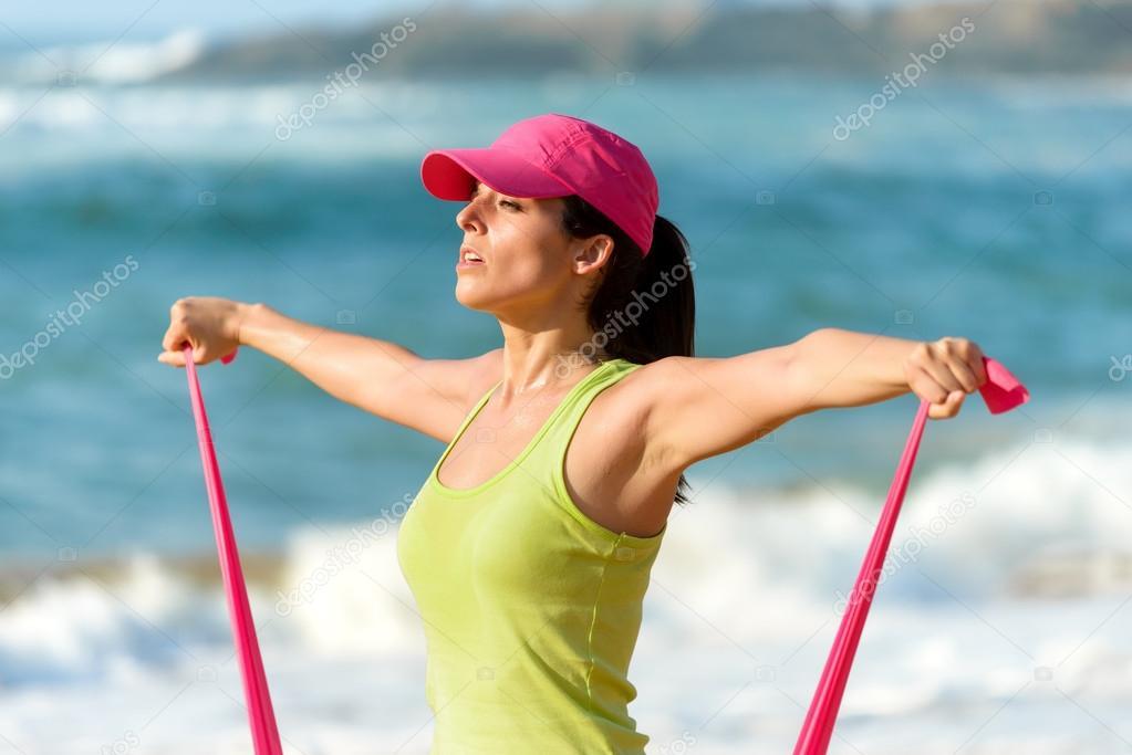 Femme exerçant et épaules avec bande de résistance de formation sur l été.  fille de remise en forme la transpiration et de travailler sur la plage —  Image ... 52bfa7edba4