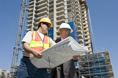 Building developer and contractor discuss progress on a hirise construction project at the job site stock vector