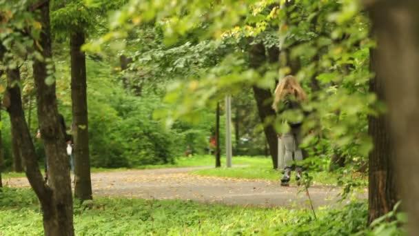 junges Mädchen Reiten entlang der Gasse des Stadtparks