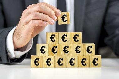 Man building a pyramid of euro symbols