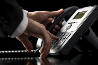 Low angle closeup view of the hands of a businessman in a suit dialing out on a telephone call using a dial-up desktop landline instrument as he presses the numbers on the keypad stock vector