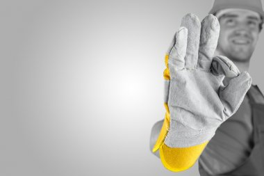 Workman making a perfect gesture with his gloved hand with focus to his hand over a grey background with a highlight and copyspace. stock vector