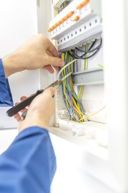 Electrician checking the wiring in a fuse box
