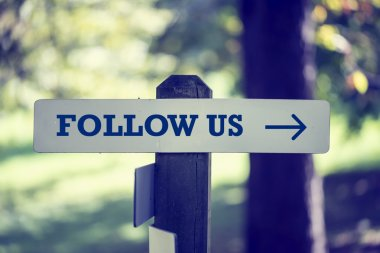 Follow Us signboard on a wooden post