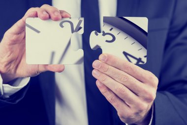 Businessman holding puzzle pieces of a clock