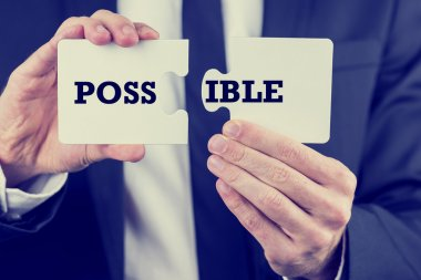 Man holding puzzle pieces with the word Possible