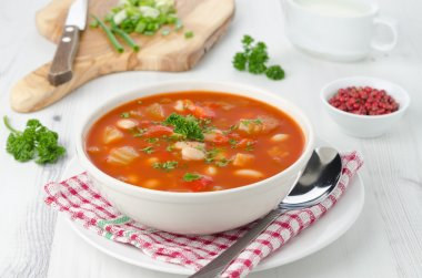 Bowl of roasted tomato soup with beans, celery and sweet pepper
