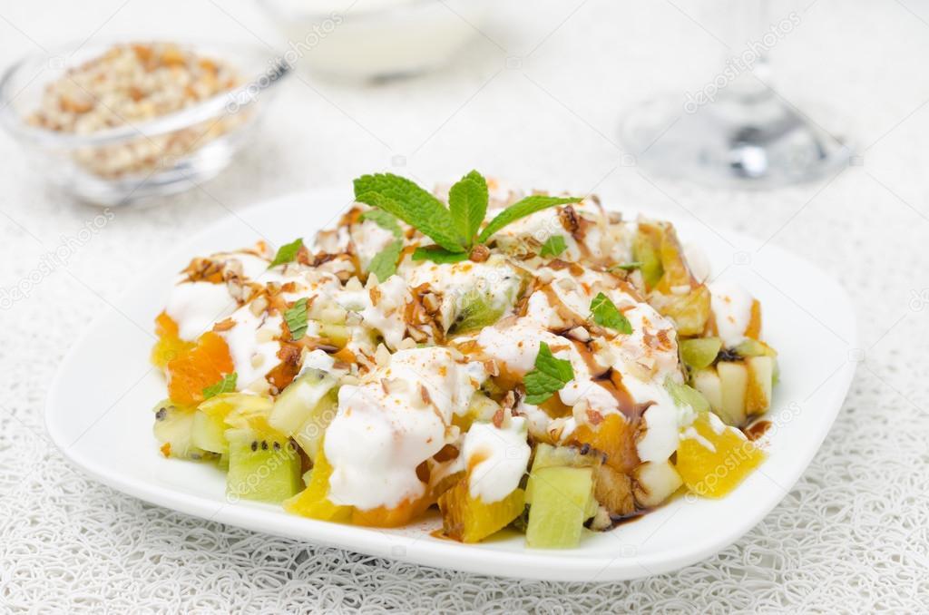 fruit salad with nuts, yogurt and mint garnished with yogurt