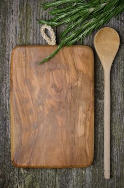 Vintage cutting board with space for text, spoon and rosemary