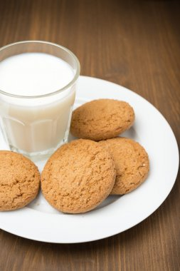 glass of milk and oat cookies on a plate, close-up