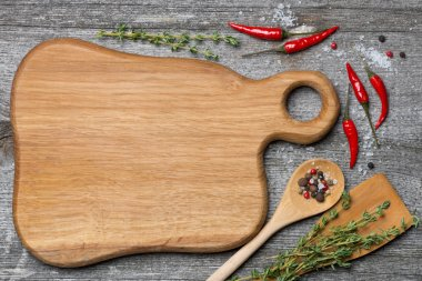 Figured wooden cutting board, spoon, spatula, herbs and spices