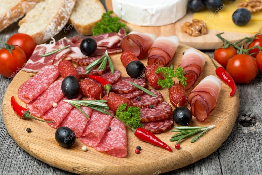 Assorted meats and sausages, olives and spices on a wooden board