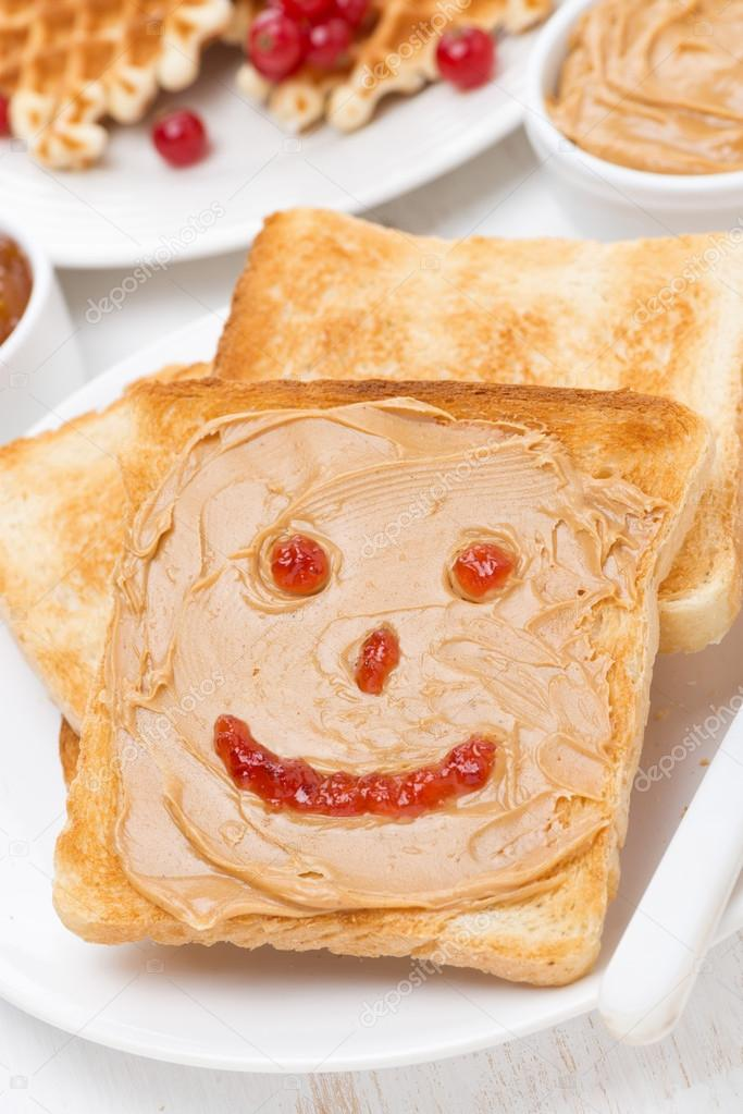 Toast with peanut butter and drawing of jam, close-up