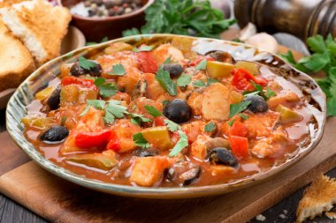 Fish stew with olives in tomato sauce on a plate, close-up