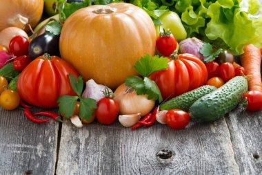 Harvest of seasonal fresh vegetables on wooden background