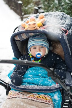 Baby boy in pram during winter snow fall