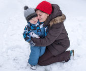 matka a batole chlapce baví se sněhem v zimě den