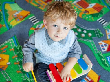 Little toddler boy playing with wooden music toy