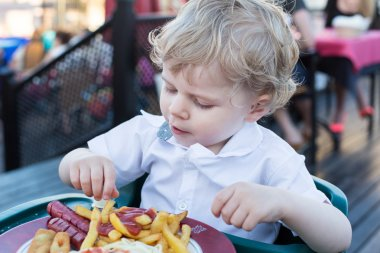 Cute little boy eating french fries in summer
