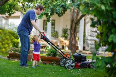 Man and his little son having fun with lawn mower in garden