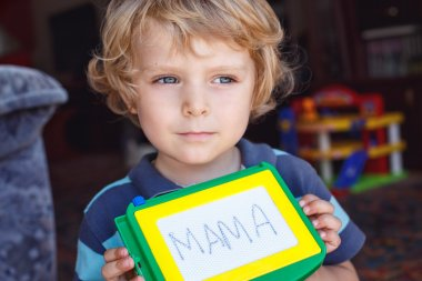 Little toddler boy with painting board writes his first word