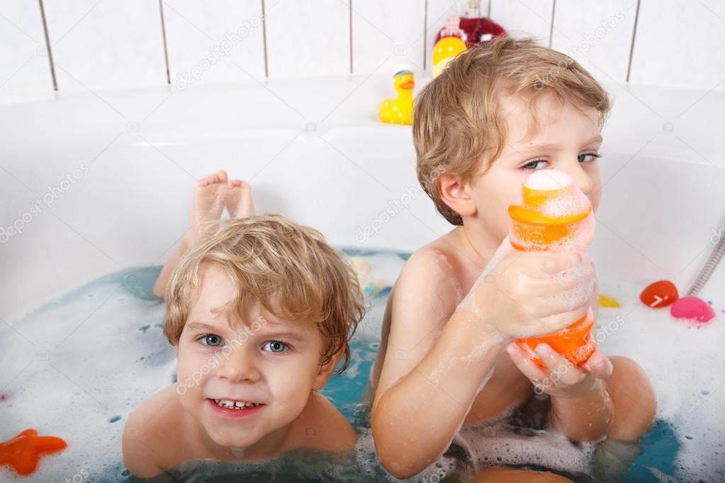 Two little twins boys having fun with water by taking bath in ba ...