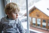 chlapeček batole při pohledu z okna na zimní den s