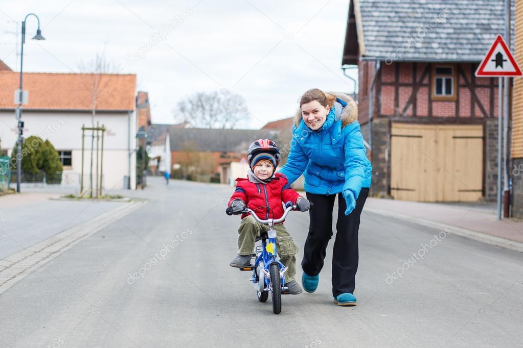 Enseñar A Los Chicos A Andar En Bici: Joven Madre Enseñando Sus 3 Años Viejo Hijo A Andar En