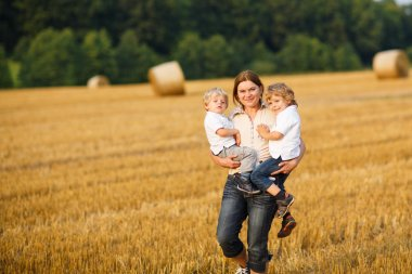 Young mother and two little twins boys having fun on yellow hay