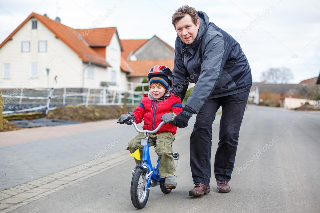 Enseñar A Los Chicos A Andar En Bici: Joven Padre Enseñando Sus 3 Años Viejo Hijo A Andar En