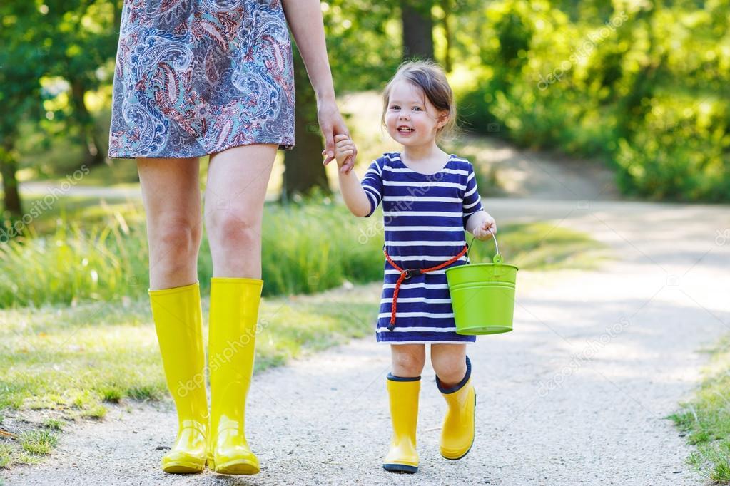 mutter und wenig liebenswert kind in gelben gummi stiefel. Black Bedroom Furniture Sets. Home Design Ideas
