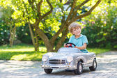 Malý kluk, venku řízení velké staré autíčko,