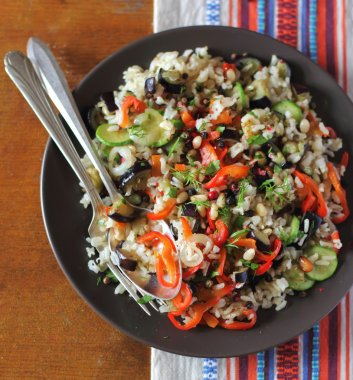 Cooked brown rice with roasted pepper, eggplant, courgette and pine nuts in a plate for healthy lunch or dinner