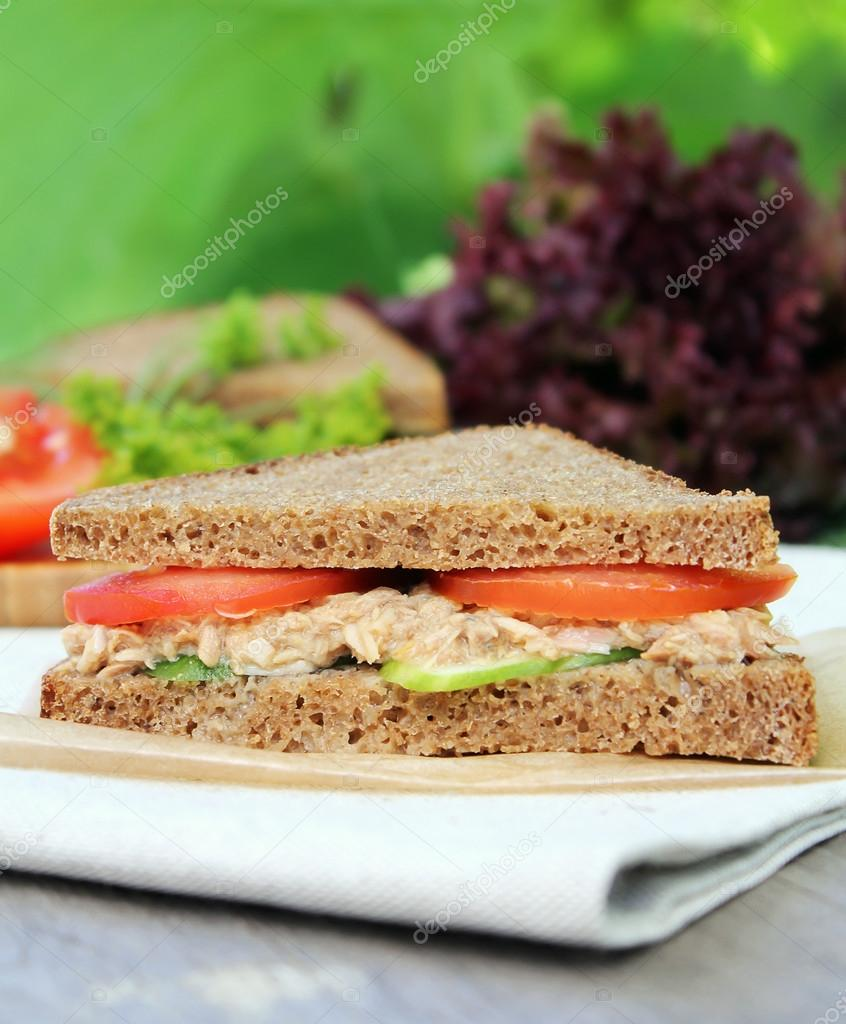 Summer picnic snack sandwich with toasted rye bread, juicy tomatoes, ripe cucumbers and canned tuna fish on a wooden table outdoors