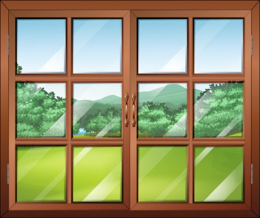 A closed window with a view of the green surroundings