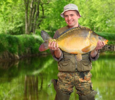 The fisherman with his big carp at a beautiful river.