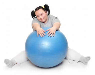 Happy overweight woman with blue ball exercising