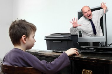 Little boy looking at computer with dangerous content.
