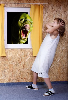 Screaming green zombie and fright little girl