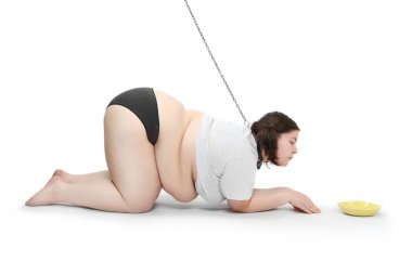 Funny picture of an hungry obese woman chained near plate with food. Diet concept.
