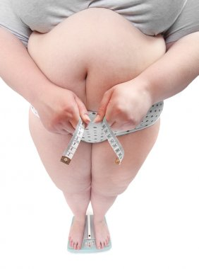 Happy overweight woman with big breast measure her waist belly by metre-stick.