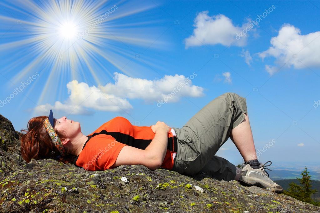 Young woman meditating on a high peak.