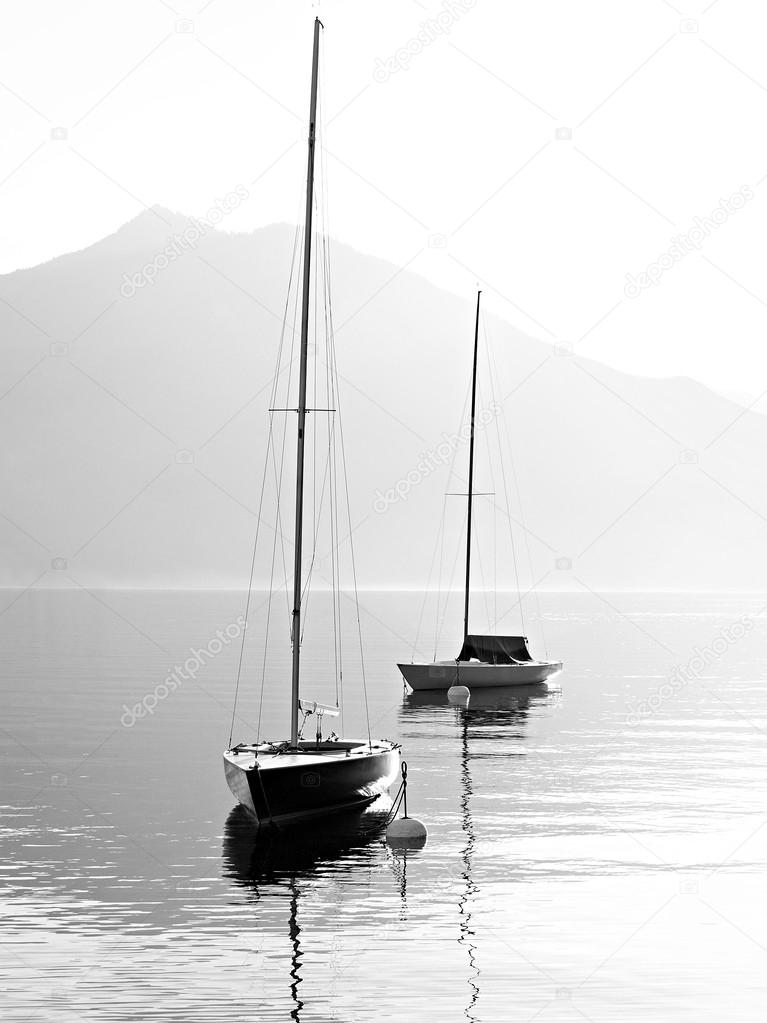 Two sail boats in early morning on the mountain lake. Black and white photography. Salzkammergut, Austria.