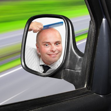 Careless driver combing hairless head