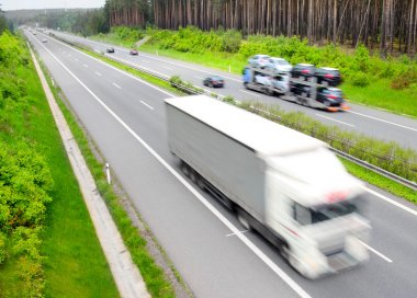 Motion blurred trucks on highway. Transportation industry concept.