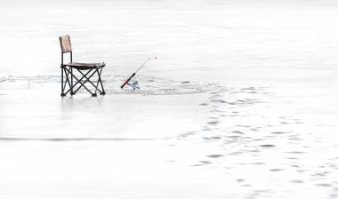 Fisherman's chair and fishing rod on a frozen lake in winter. Leisure background.