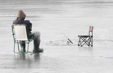 Young fisherman catching a fish on a frozen lake in winter.