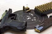 Gun and ammunition over bullseye score