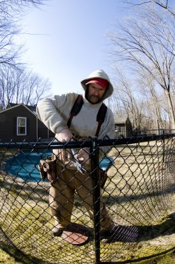 workman repairing building chain link fence