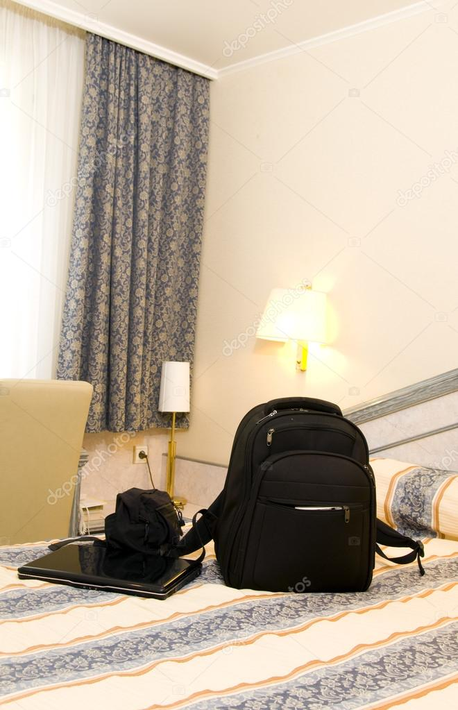 Hotel Room With Backpack And Laptop On Bed